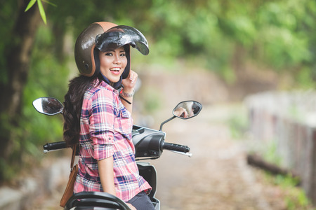 A portrait of a young asian woman riding a motorcycle in a park Stock Photo