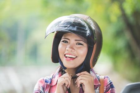 casco moto: Un retrato de una mujer asiática joven que llevaba un casco antes de conducir una motocicleta en un parque