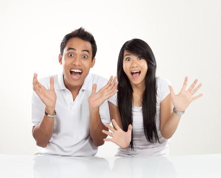 berros: Un retrato de una pareja asiática joven con expresión de sorpresa feliz, mirando a la cámara