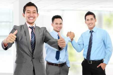 shake up: businessman showing thumb up while his team shake hand at the background. success business deal Stock Photo