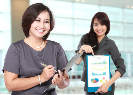 A portrait of a happy mature business women, with her assistant showing a graphic on clipboard photo