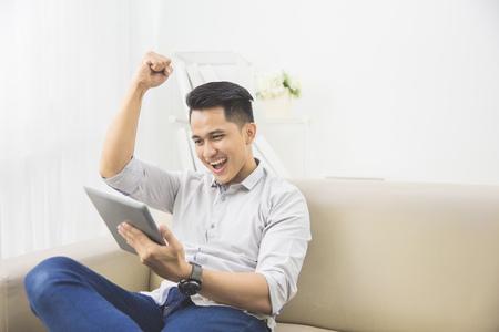 hombres jovenes: joven excitado feliz con la tableta levantó el brazo en su casa sentado en un sofá