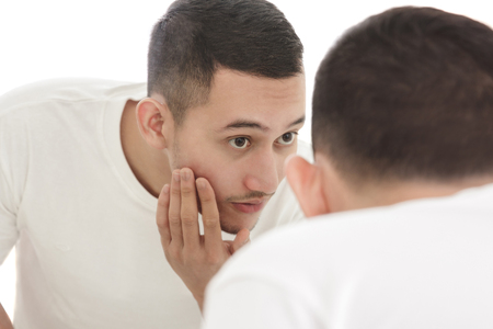 asian guy: portrait of handsome man looking into the mirror and touching his smooth face