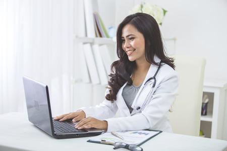 examenes de laboratorio: sonriendo asiático médico femenino que trabaja en la oficina Foto de archivo