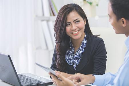 Beeld van twee jonge Aziatische mensen uit het bedrijfsleven op de bijeenkomst in het kantoor
