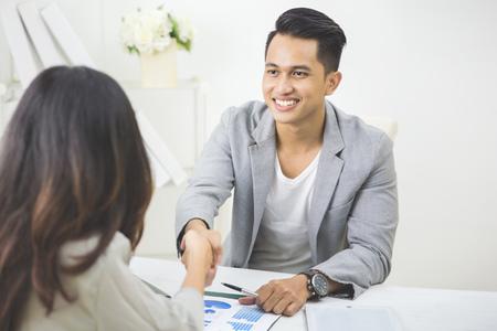 Portret van business partner maken een deal in het kantoor. hand schudden