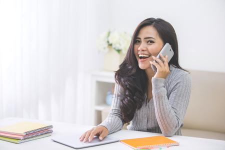 reir: retrato de la mujer asiática ocasional hacer una llamada telefónica en su casa usando teléfonos inteligentes Foto de archivo