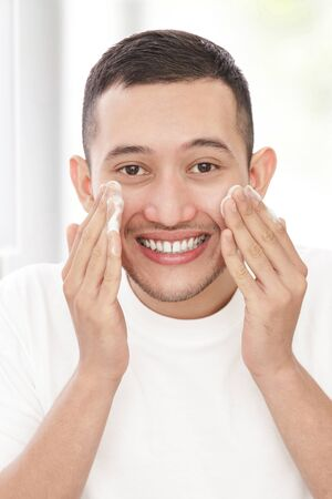 portrait of handsome man washing his face using facial foam