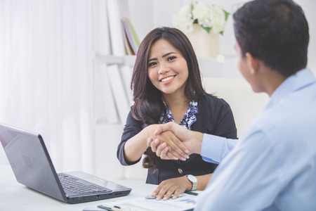 two men: Pretty asian business woman shaking hands with businessman in her office during meeting