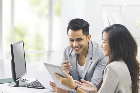 2 つのビジネスの人々 の肖像画は、オフィスでタブレット pc を使用してビジネスの話します。