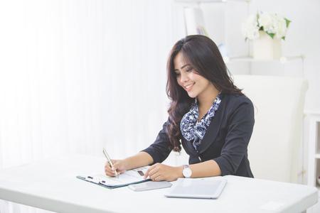 Jong lachend zakelijke vrouw werkt op haar papierwerk in haar kantoor Stockfoto