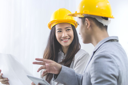 young asian: business, partnership, architecture and people concept - smiling businessman and businesswoman with blueprint and helmets discussing