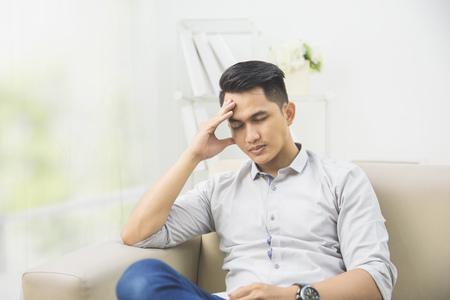 cansancio: Retrato de hombre joven con problemas y el estrés en su casa sentado en un sofá