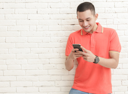 portrait of handsome man texting on mobilephone with copy space on white brick wall background