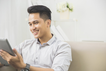 portrait of handsome asian man using tablet pc at home