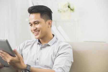 portrait d'un homme beau asiatique en utilisant la tablette pc à la maison Banque d'images