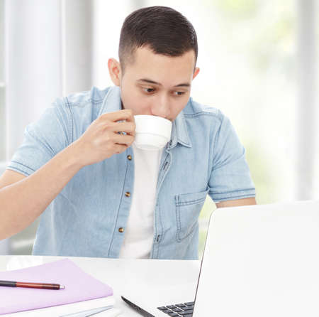 man studying: portrait of young man drinking a cup of tea while studying Stock Photo