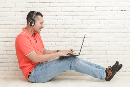 portrait of handsome college student playing game on laptop while sitting on the floor Stock Photo