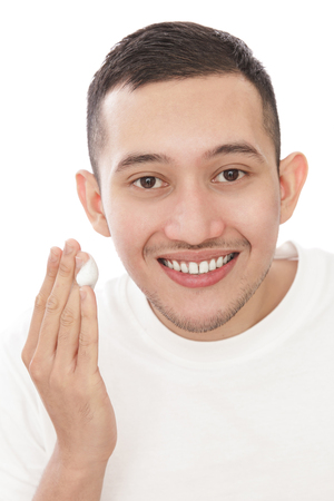 smile close up: close up portrait of handsome man applying facial foam while smiling isolated on white background