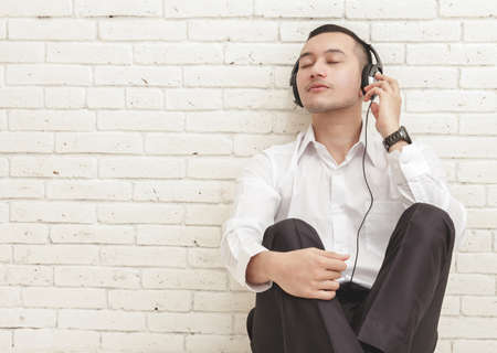 enjoy space: portrait of young businessman enjoy listening music using headphones with copy space on white brick wall background