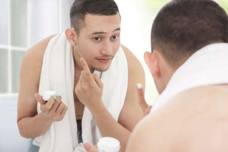 asian adult: portrait of handsome man applying moisturizer cream to his face