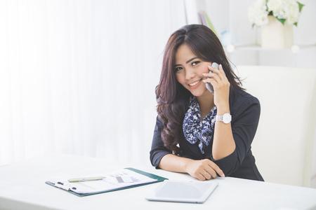 笑顔のビジネス女性がオフィスに坐っている間携帯電話を使用して