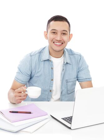 man studying: portrait of handsome young man studying on laptop while holding a cup of tea isolated on white background Stock Photo