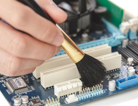 fermer les mains d'un technicien de nettoyage le matériel de l'ordinateur en utilisant une brosse