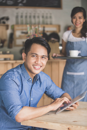 asian business man: Image of happy young man using digital tablet in cafe Stock Photo