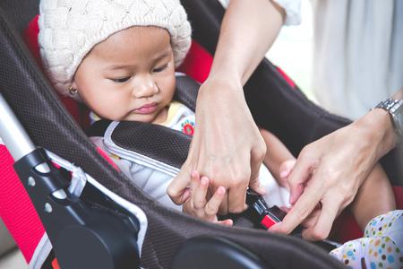 viaje familia: Retrato de una madre asegurando su bebé en el asiento de seguridad en su coche