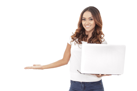 girl with laptop: portrait of casual young woman presenting copy space while holding a laptop isolated on white background