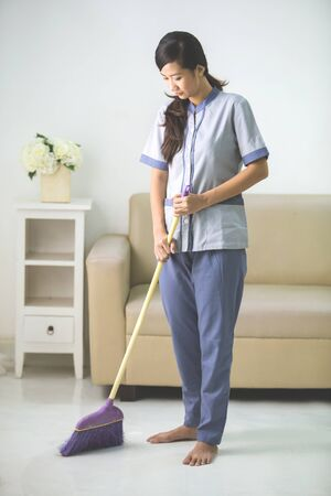 bioclean: cleaner maid woman with sweep and uniform cleaning living room at home Stock Photo