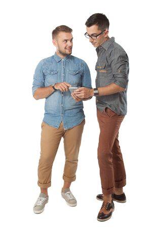 two men: A portrait of two cheerful young man dicussing something on the cellphone and smiling Stock Photo