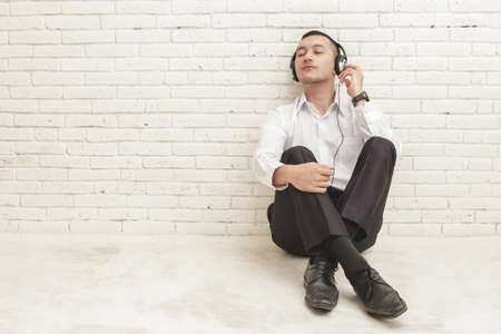 enjoy space: full body portrait of young businessman enjoy listening music using headphones with copy space on white brick wall background