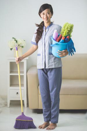 domestico: retrato de mujer joven y bella asiática de limpieza de limpieza sonriendo a la cámara