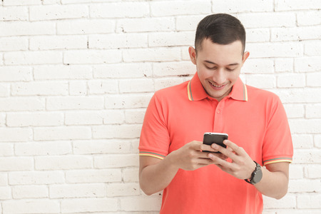 mobilephone: portrait of handsome young man texting on mobilephone with copy space on white brick wall background Stock Photo