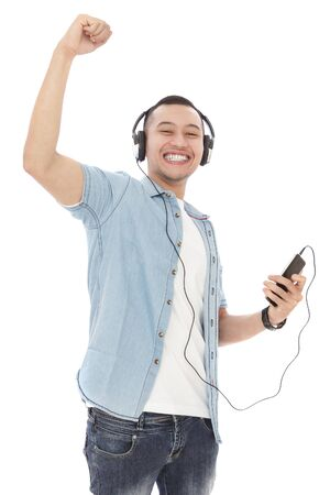 asian lifestyle: portrait of cheerful young man enjoy listening music on mobilephone with headphones isolated on white background