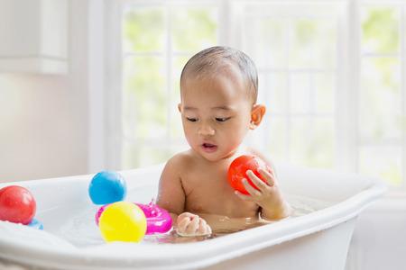 bañarse: bañar a un bebé asiático en la bañera blanca. sonriendo y jugando con su juguete