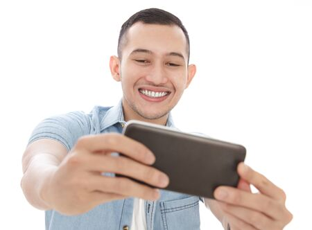 asian guy: portrait of casual man smiling while taking selfie photo using mobilephones camera isolated on white background