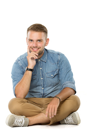 handsome young man: A portrait of a smiling guy sitting on the floor, isolated over white.