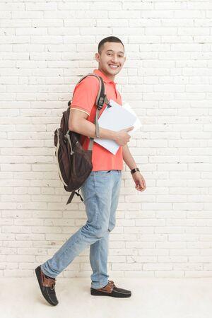 persona caminando: retrato de cuerpo entero de los estudiantes universitarios hermoso que lleva a algunos libros mientras wallking Foto de archivo