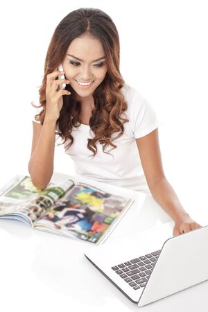 view girl: portrait of multitasking young woman talking on the phone while working on her laptop isolated on white background