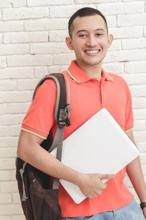 hombres jovenes: retrato de los estudiantes universitarios hermoso que lleva un ordenador portátil