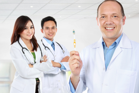 man doctor: dentist showing brush. medical doctor with colleague at the background