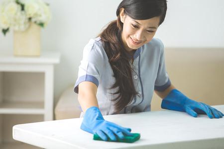 Donna di pulizia detergente con scopa indossando tavolo di pulizia uniformi in salotto a casa Archivio Fotografico - 54109984