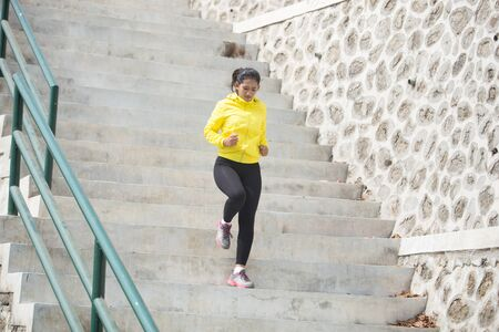 climb: A portrait of a Young asian woman exercising outdoor in yellow jacket, jogging going up and down the stair Stock Photo