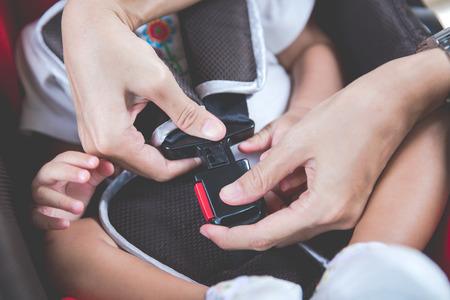 Protection dans la voiture. Mains de la femme réside dans la fixation ceinture de sécurité pour bébé dans le siège de voiture