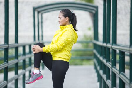 woman stretching: A portrait of a young asian woman exercising outdoor in yellow neon jacket, stretching