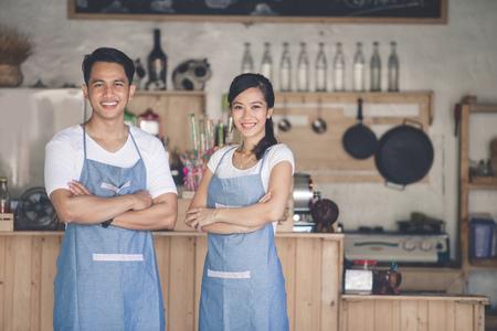 성공적인 중소 기업 소유자는 자랑스럽게 자신의 카페 앞에 서