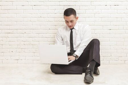 young businessman: portrait of young businessman working on laptop while sitting on the floor with white brick wall background Stock Photo